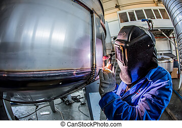 Man welding with reflection of sparks on visor. Hard job....