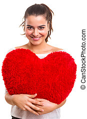 Valentines day concept - Young woman with a heart pillow in...