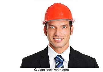 Smiling handsome businessman in a protective helmet, left...