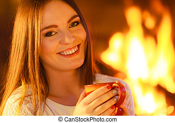 girl warming up at fireplace holds - winter at home, heating...
