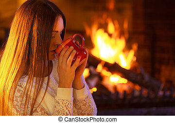 Girl warming up at fireplace holds mug - Winter at home,...