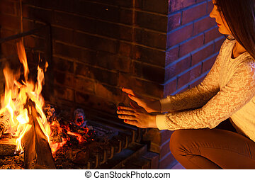girl warming her hands at fireplace