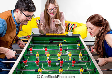 Friends playing table football - Young friends or students...