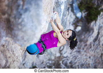 Female rock climber on a cliff face - Young female rock...