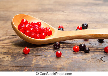 viburnum and black currant on wooden spoon - viburnum in...