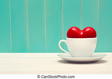 Coffee filled with love on vintage style teal wood...