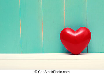Red shiny heart on vintage teal wood background