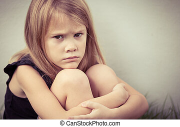 Portrait of sad blond little girl sitting near wall on...