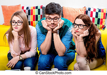 Three nerds on the couch - Three nerds in eyeglasses sitting...