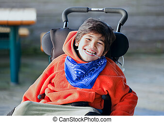 Handsome, happy biracial eight year old boy smiling in wheelchai