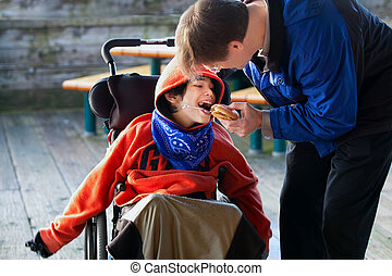 Father feeding disabled son a hamburger in wheelchair. Child has