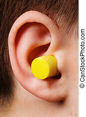 yellow earplug into the ear close up