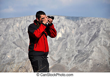 Photographer shooting pictures in the mountains