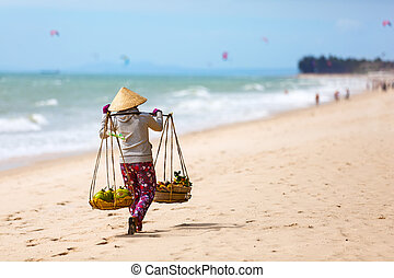 Vietnamese woman selling Fruits at Mui Ne beach. Vietnam....