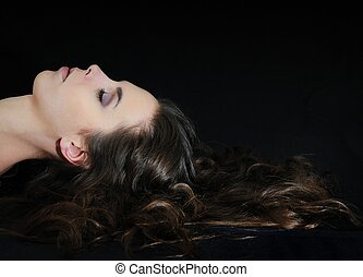 Young woman lying on black with long hair