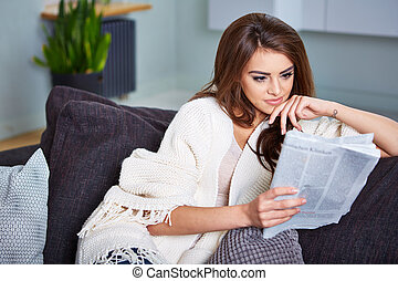 Young Happy Woman Reading Newspaper On Couch
