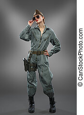 Sexy girl dressed as a helicopter pilot posing in sunglasses...
