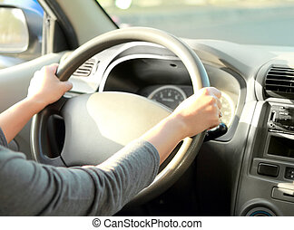woman with her hand on the wheel steering