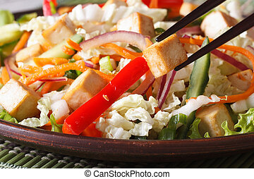 Healthy salad tofu and vegetables with chopsticks macro on a...