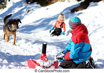 children and dog in snow