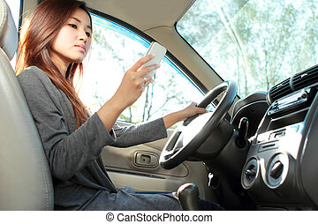 young woman texting while driving - portrait of young beauty...
