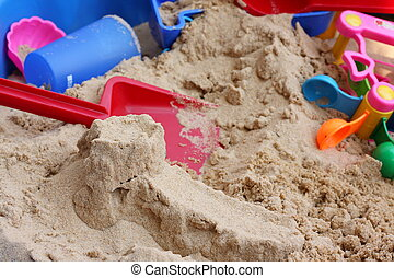 Sandpit with colorful toys - Colorful toys lie piled...