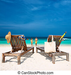 Couple in yellow running on a beach at Maldives - Couple in...