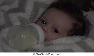 Baby Feeding in Dark - Baby in feeding bottle close-up view...