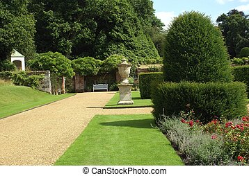 garden pathway with an urn, bench, topiary, and flowers