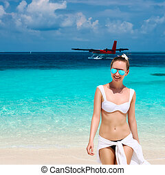 Woman at beach. Seaplane at background. - Woman in bikini at...