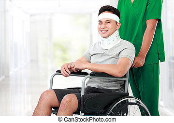nurse pushing young patient in wheelchair