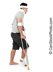 young man with broken leg on crutch - side view of young man...