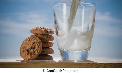 Cookies and glass of milk, on wooden table. Close up