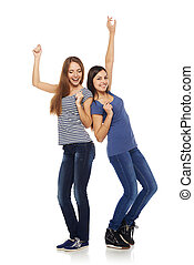 Success - Two happy young girls friends dancing of joy in...