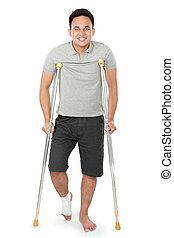 joven, hombre, con, roto, pierna, uso, muletas,