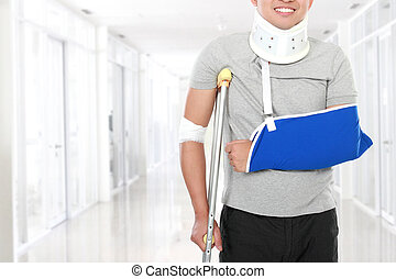 injured young man use crutch and arm sling - portrait of...