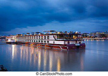 The ship sails on the Danube in Budapest at evening time