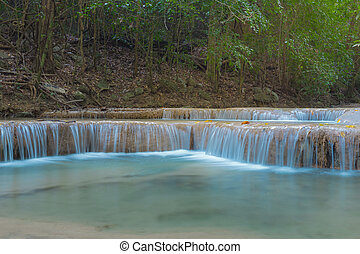 Blue stream waterfall - A stream flowing through foggy...