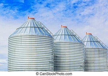Steel Grain Bins - A row of steel grain bins used by farmers...