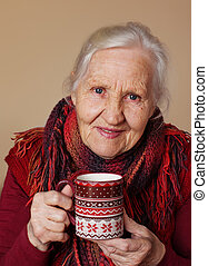 Elderly woman with cup of hot tea