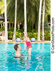 Active father teaching his toddler daughter to swim in pool...