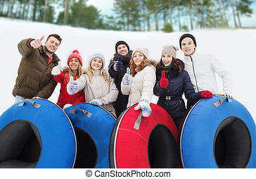 group of smiling friends with snow tubes - winter, leisure,...