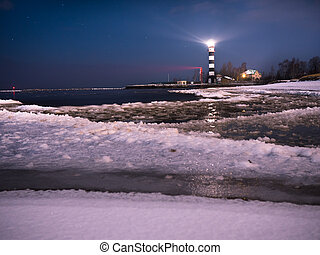 Riga Lighthouse in a starry night with frozen Baltic sea