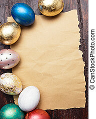 Easter eggs on wooden table with blank paper for text...