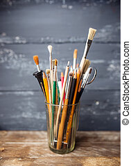 Photo of paint brushes in a glass standing on old wooden...