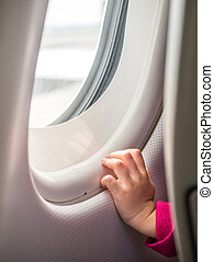 Childs hand touching airplane window in concept of the first...