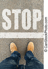 man on a tarmac road with the word Stop Stopping human way...