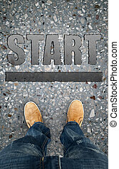 man on a tarmac road with the word Start. A concept of...