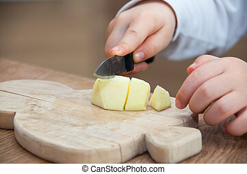 Child cutting an apple on wooden table