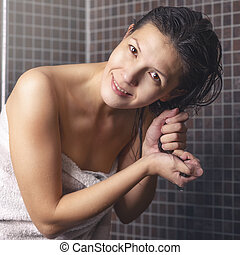 Smiling Woman after Shower Holding her Wet Hair - Close up...